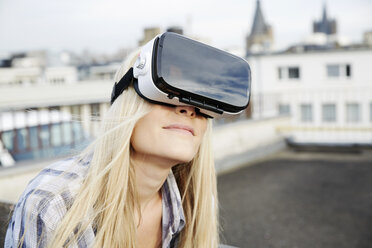 Portrait of woman wearing Virtual Reality Glasses outdoors - FMKF04763