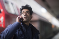 Portrait of man on the phone waiting on platform - SGF02170