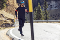 Man running on mountain road - PNEF00437