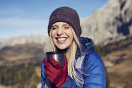 Portrait of happy woman holding mug in the mountains - PNEF00446