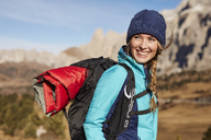 Portrait of happy young woman hiking in the mountains - PNEF00449