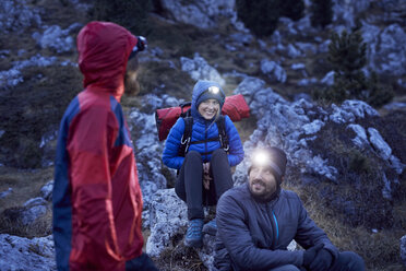 Smiling mountaineers wearing headlamps in the mountains at dusk - PNEF00458