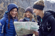 Three happy young women hiking in the mountains looking at map - PNEF00461