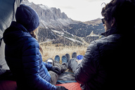 Couple sitting in tent in the mountains looking at view - PNEF00470