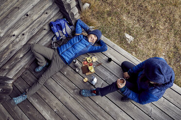 Overhead view of couple hikers having a break at mountain hut - PNEF00473