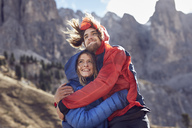 Happy young couple hugging in windy mountains - PNEF00482