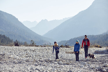 Germany, Bavaria, Karwendel, group of friends hiking with dog in dried riverbed - PNEF00485