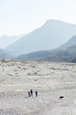 Germany, Bavaria, Karwendel, group of friends hiking with dog in dried riverbed - PNEF00488