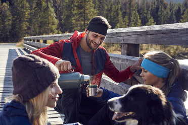 Group of friends with dog hiking resting on a bridge - PNEF00494