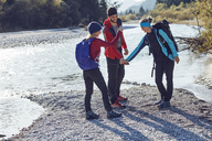 Group of friends hiking shaking hands at the riverside - PNEF00500