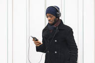 Italy, Milan, African american man with smartphone and headphone - MAUF01278