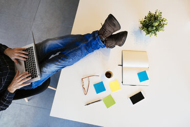 Businessman using laptop with feet on desk in office - EBSF02095