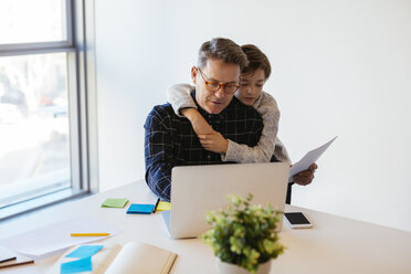 Businessman using laptop at desk in office with son embracing him - EBSF02098