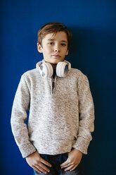 Portrait of boy wearing headphones at blue wall - EBSF02104