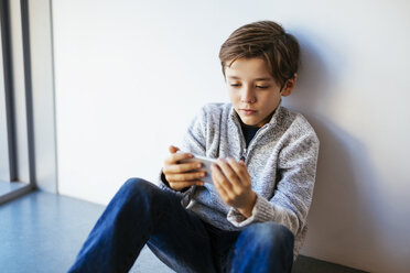 Boy sitting on floor looking at cell phone - EBSF02110