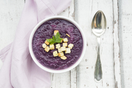 Bowl of red cabbage soup garnished with croutons and leaf of parsley - LVF06661