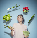 Portrait of happy young woman juggling with vegetables - PNEF00518
