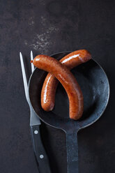 Two minced pork sausage in pan and a meat fork on rusty metal - CSF28846