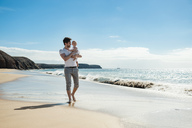 Spain, Lanzarote, father carrying his little daughter on the beach - DIGF03224