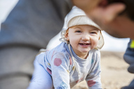 Spain, Lanzarote, portrait of laughing baby girl playing with father on the beach - DIGF03230