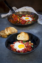Shakshouka with chick peas in pan and slices of baguette - LVF06669