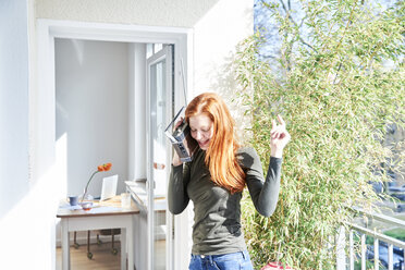 Happy woman dancing with radio on balcony - FMKF04766