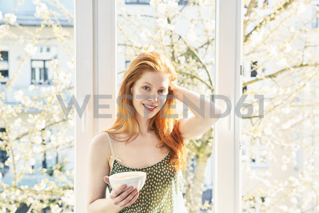 Portrait of redheaded woman with bowl of white coffee in front of window - FMKF04772 - Jo Kirchherr/Westend61