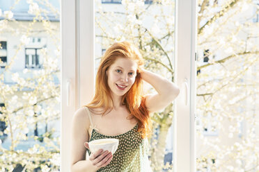 Portrait of redheaded woman with bowl of white coffee in front of window - FMKF04772