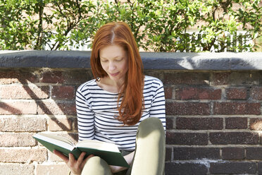 Portrait of redheaded woman reading a book outdoors - FMKF04775