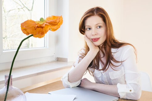 Portrait of redheaded woman at home office - FMKF04778