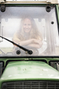 Portrait of smiling woman sitting in a tractor - PESF00941