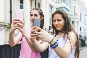 Two teenage girls in the city standing side by side taking selfies - WPEF00010