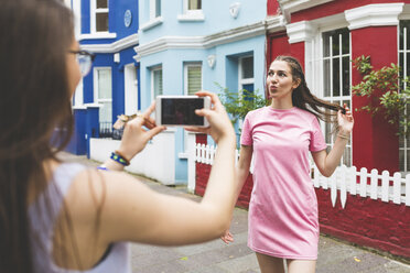 Teenage girl taking cell phone picture of young woman in the city - WPEF00016