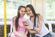 Two happy teenage girls sharing cell phone in subway - WPEF00019