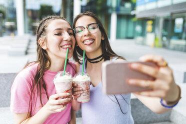 Two happy teenage girls drinking milkshakes in the city taking a selfie - WPEF00028