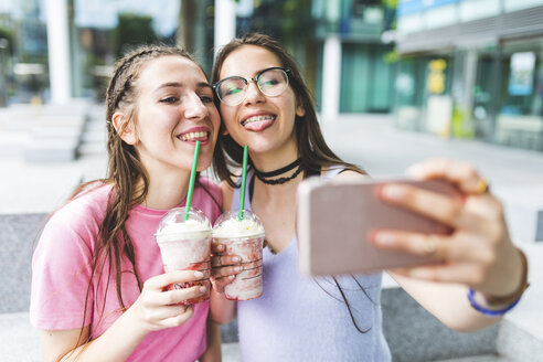 Two happy teenage girls drinking milkshakes in the city taking a selfie - WPEF00028