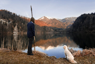 Austria, St. Gilgen, Krottensee in autumn, young man with dog - WVF00923