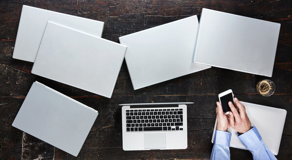 Man's hands using smartphone on table with seven laptops, top view - FMKF04786