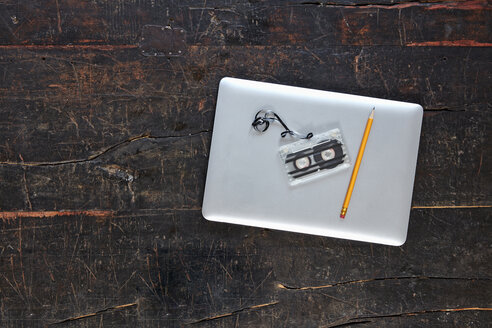 Laptop, tape and pencil on wooden tabletop, top view - FMKF04789