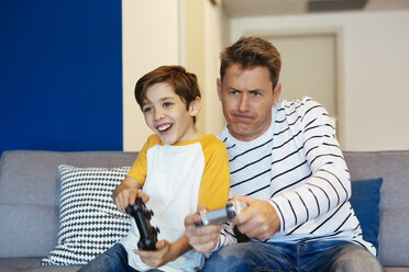 Father and son playing video game on couch at home - EBSF02113