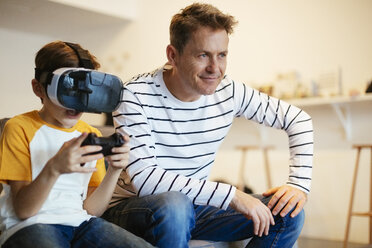 Boy wearing VR glasses playing video game with father on couch at home - EBSF02116