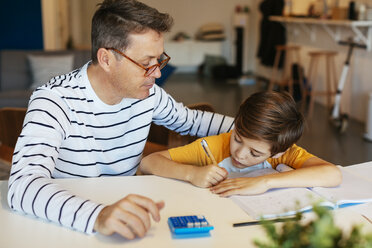 Father watching son doing homework at table - EBSF02119
