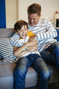 Carefree father and son having fun on couch at home - EBSF02125