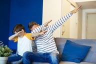 Father and son making a dab on couch at home - EBSF02128