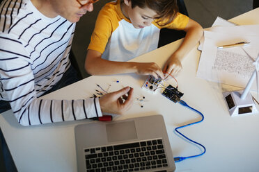Father and son assembling a construction kit with laptop and wind turbine model - EBSF02131