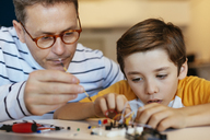 Father and son assembling an electronic construction kit - EBSF02134