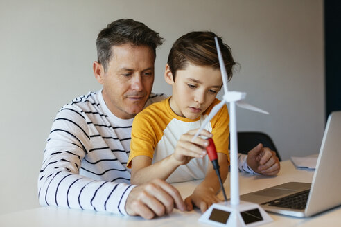 Father and son with laptop assembling wind turbine model - EBSF02137