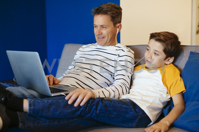 Father and son with earbuds and laptop on couch at home - EBSF02140