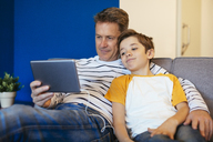 Father and son with earbuds and tablet on couch at home - EBSF02143