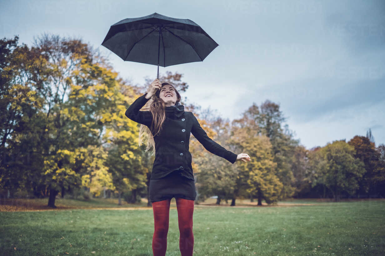 Young woman with umbrella in autumnal park - JSCF00027 - Jonathan Schöps/Westend61